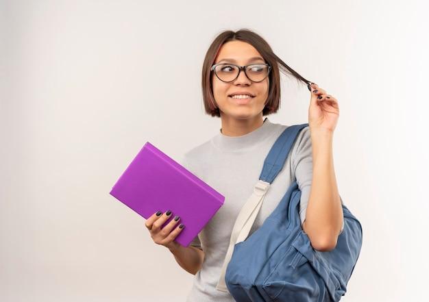 Улыбающаяся молодая студентка в очках и задней сумке держит книгу и ее волосы, смотрящие в сторону, изолированную на белой стене