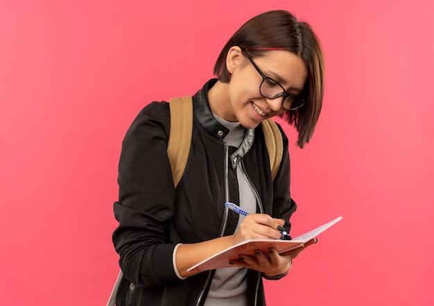 Улыбающаяся молодая студентка в очках и спине с сумкой пишет что-то в блокноте, изолированном на розовой стене