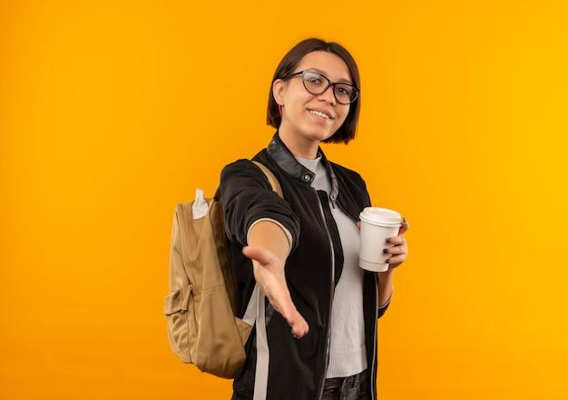 Sorridente ragazza giovane studente con gli occhiali e borsa posteriore che tiene tazza di caffè di plastica che allunga la mano verso la parte anteriore che gesturing ciao isolato sulla parete arancione
