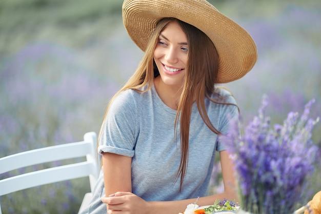 ラベンダー畑でポーズをとって笑顔の若い見事な女性