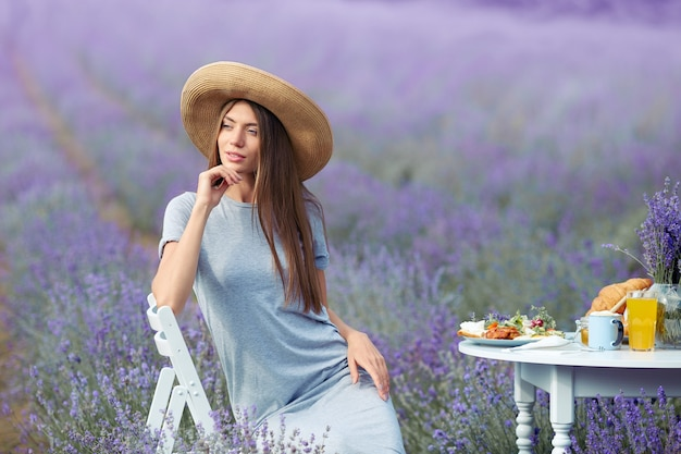 Smiling young stunning woman posing in lavender field