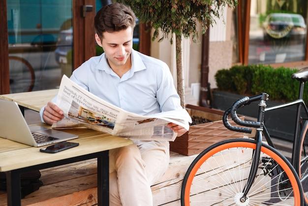 Улыбающийся молодой стильный мужчина в рубашке читает газету