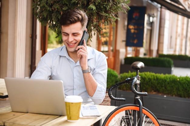 携帯電話で話しているシャツの若いスタイリッシュな男の笑顔