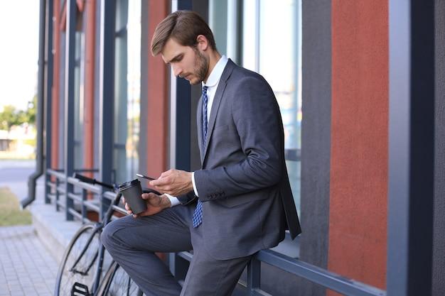 Улыбающийся молодой стильный человек с помощью мобильного телефона попивая кофе на открытом воздухе с велосипедом.