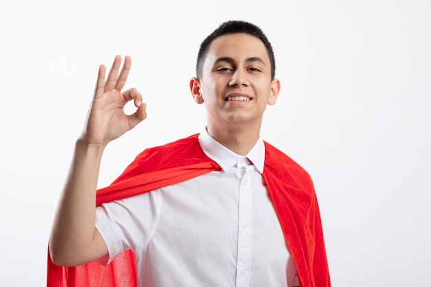 Smiling young superhero boy in red cape looking at camera doing ok sign isolated on white background with copy space
