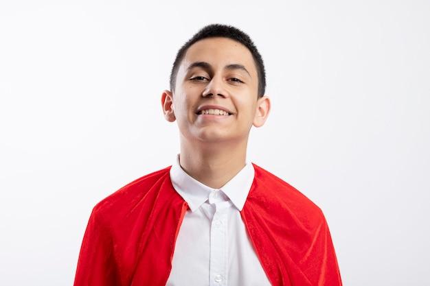 Ragazzo giovane supereroe sorridente in mantello rosso che guarda l'obbiettivo isolato su priorità bassa bianca