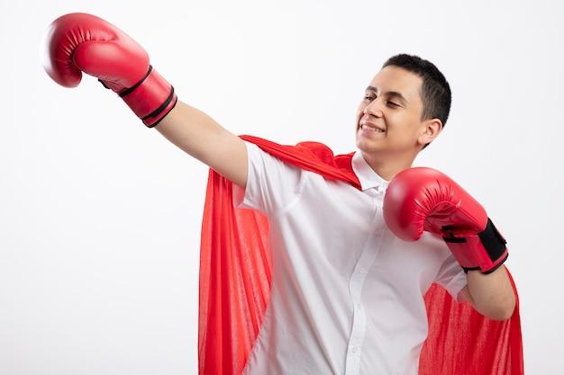Sorridente giovane supereroe ragazzo in mantello rosso che indossa guanti di scatola allungando la mano mantenendo un altro in aria guardando il lato isolato su sfondo bianco