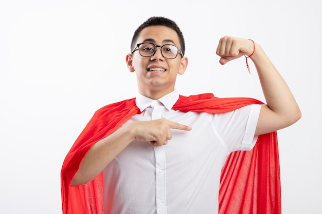Smiling young superhero boy in red cape wearing glasses looking at camera doing strong gesture pointing at muscles isolated on white background