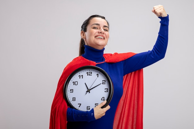 Улыбающаяся молодая девушка супергероя держит настенные часы, показывая сильный жест, изолированные на белом фоне