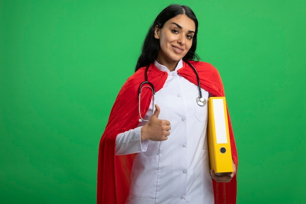 Smiling young superhero girl wearing medical robe with stethoscope holding folder showing thumb up isolated on green