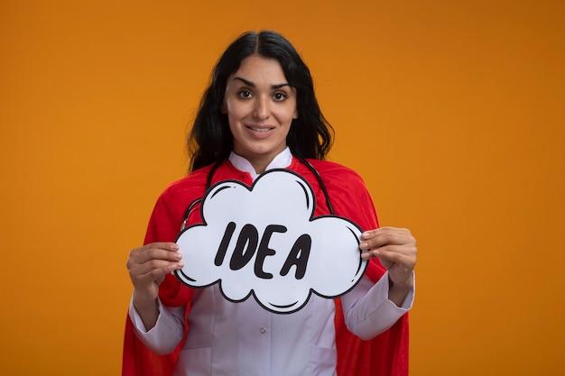 Улыбающаяся молодая девушка-супергерой в медицинском халате со стетоскопом держит пузырь идеи, изолированный на оранжевом