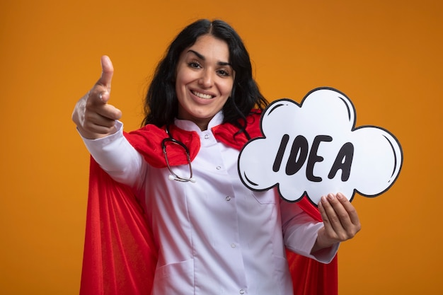 Улыбающаяся молодая девушка-супергерой в медицинском халате со стетоскопом держит пузырь идеи, показывая вам жест, изолированный на оранжевом