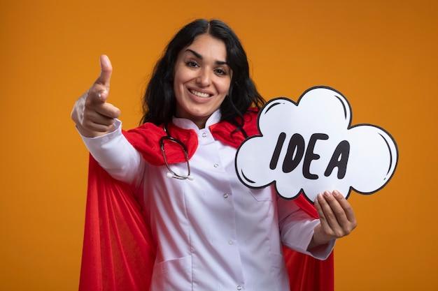 Sorridente giovane ragazza del supereroe che indossa abito medico con lo stetoscopio che tiene la bolla di idea che mostra il gesto isolato sull'arancio
