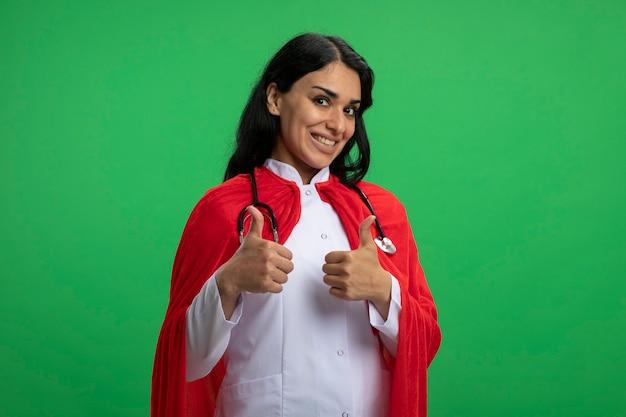 Sorridente giovane ragazza del supereroe che indossa abito medico con lo stetoscopio che mostra i pollici in su isolato sul verde