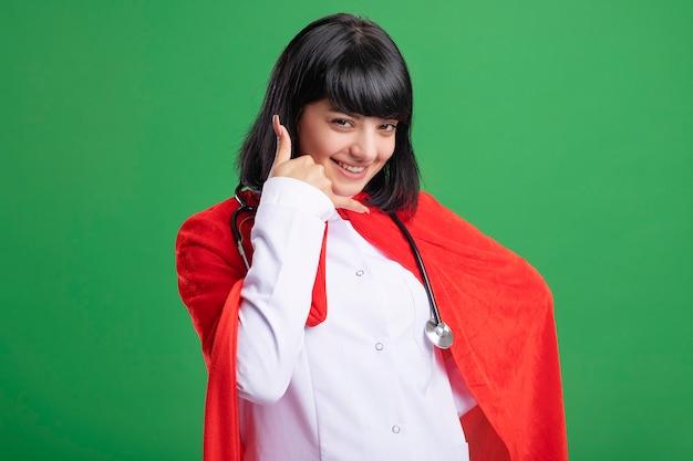 의료 가운과 녹색 벽에 고립 된 전화 제스처를 보여주는 망토 청진기를 입고 젊은 슈퍼 히어로 소녀 미소