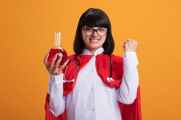 聴診器と医療用ローブとマントを身に着けている笑顔の若いスーパーヒーローの女の子は、はいジェスチャーを示す赤い液体で満たされた化学ガラス瓶を保持している眼鏡をかけています