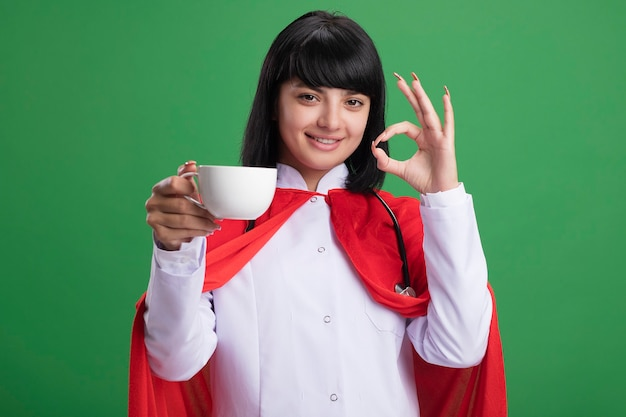 Smiling young superhero girl wearing stethoscope with medical robe and cloak holding cup of tea showing okay gesture isolated on green wall