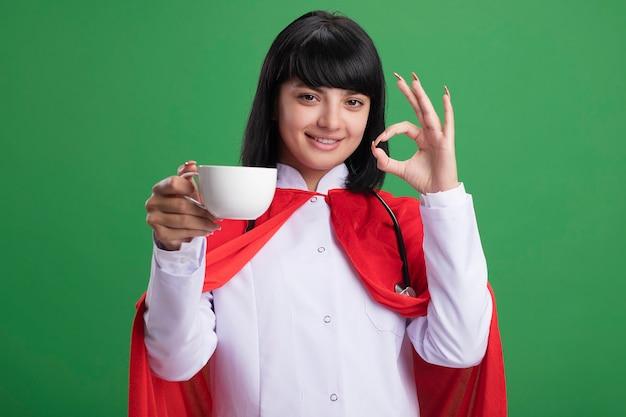 Stetoscopio d'uso sorridente della giovane ragazza del supereroe con la veste medica e il mantello che tengono la tazza di tè che mostra il gesto giusto isolato sulla parete verde