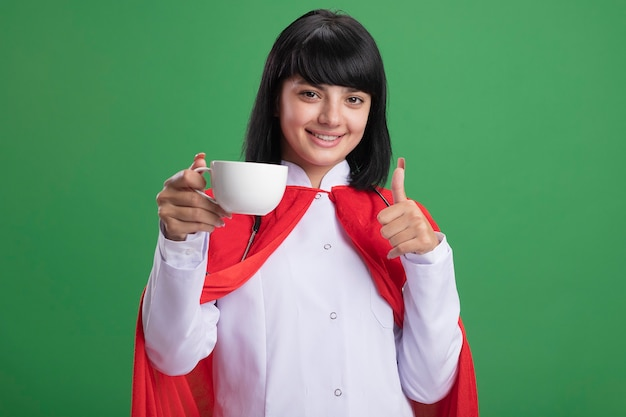Smiling young superhero girl wearing stethoscope with medical robe and cloak holding cup of tea showing thumb up isolated on green