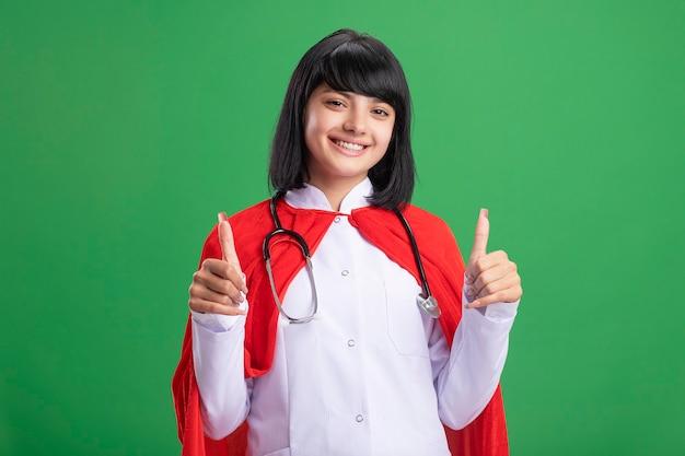 Sorridente giovane ragazza del supereroe che indossa uno stetoscopio con abito medico e mantello che mostra i pollici in su isolato sul verde