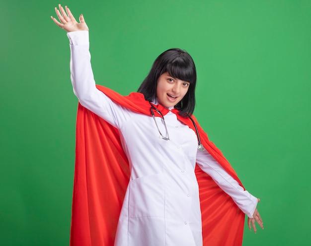 Sorridente giovane ragazza del supereroe che indossa uno stetoscopio con abito medico e mantello diffondendo le mani isolate su verde