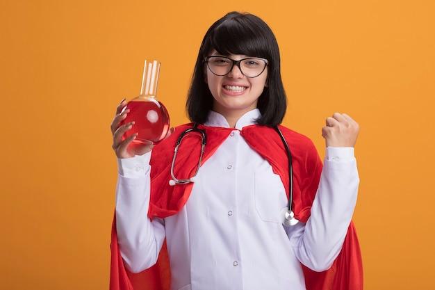 Sorridente giovane ragazza del supereroe che indossa uno stetoscopio con veste medica e mantello con gli occhiali che tengono la bottiglia di vetro chimica riempita con liquido rosso che mostra il gesto di sì