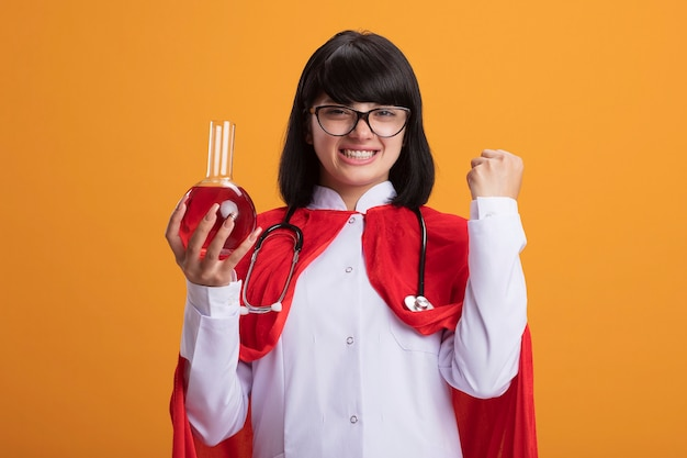 Smiling young superhero girl wearing stethoscope with medical robe and cloak with glasses holding chemistry glass bottle filled with red liquid showing yes gesture