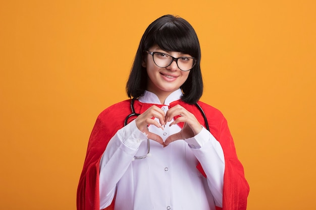 Sorridente giovane ragazza del supereroe che indossa uno stetoscopio con abito medico e mantello con gli occhiali che mostra il gesto del cuore