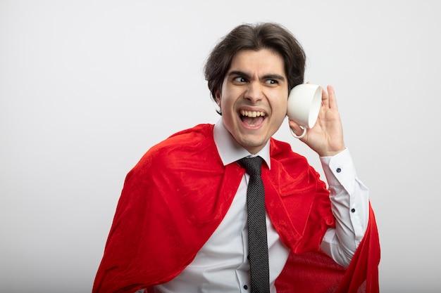 Sorridente giovane supereroe ragazzo guardando il lato che indossa la cravatta che mostra ascolta gesto con tazza isolato su sfondo bianco