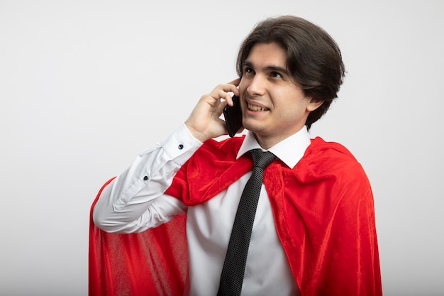 Sorridente giovane supereroe ragazzo guardando il lato che indossa la cravatta parla al telefono isolato su sfondo bianco
