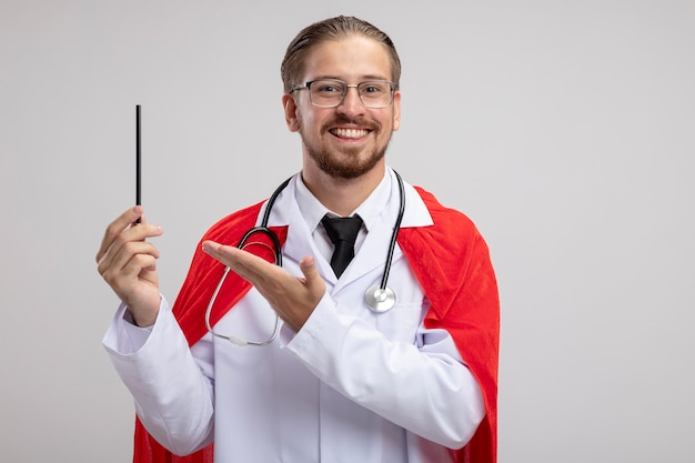 청진 기 및 안경 들고와 흰색 배경에 고립 된 연필에 손으로 포인트 의료 가운을 입고 웃는 젊은 슈퍼 히어로 남자