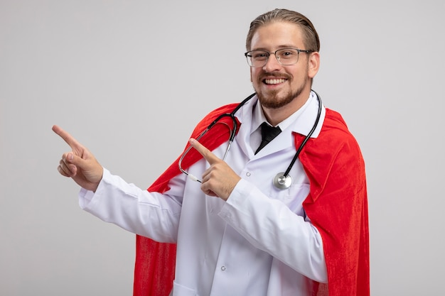 청진 기 및 안경 포인트 복사 공간 흰색 배경에 고립 된 측면에서 의료 가운을 입고 웃는 젊은 슈퍼 히어로 남자
