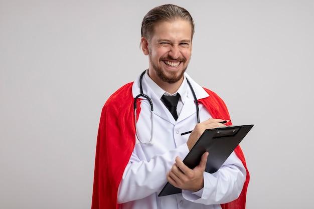 흰색 배경에 고립 된 연필로 클립 보드를 들고 청진 기 의료 가운을 입고 웃는 젊은 슈퍼 히어로 남자
