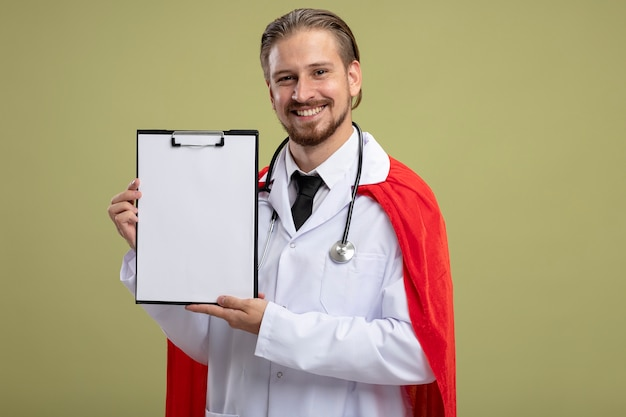 Smiling young superhero guy wearing stethoscope with medical robe holding clipboard isolated on olive green background