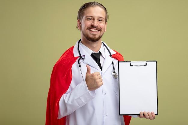 Улыбающийся молодой супергерой со стетоскопом в медицинском халате, держащий буфер обмена, показывающий большой палец вверх, изолированный на оливково-зеленом фоне