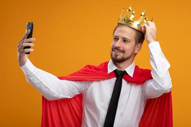 넥타이와 왕관을 착용하고 왕관에 손을 넣어 웃는 젊은 슈퍼 히어로 남자와 오렌지 배경에 고립 된 셀카 걸릴