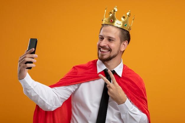 平和のジェスチャーを示すネクタイと王冠を身に着けている笑顔の若いスーパーヒーローの男は、オレンジ色に分離された自分撮りを取ります