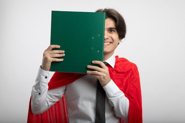 Sorridente giovane supereroe ragazzo indossa cravatta viso coperto con appunti isolati su sfondo bianco