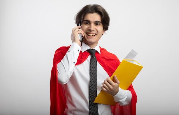 フォルダーを保持しているネクタイを着て、白で隔離の電話で話す若いスーパーヒーローの男を笑顔