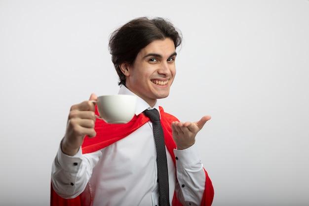 カメラで手とコーヒーのカップを差し出してネクタイを着て笑顔の若いスーパーヒーローの男