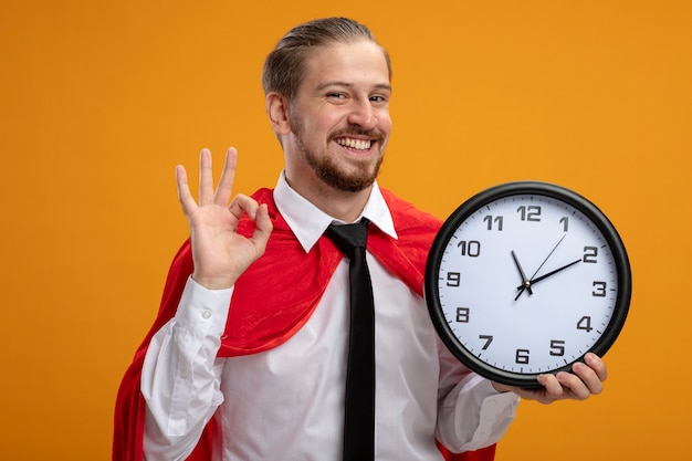 Улыбающийся молодой супергерой в галстуке держит настенные часы и показывает нормальный жест, изолированный на оранжевом фоне