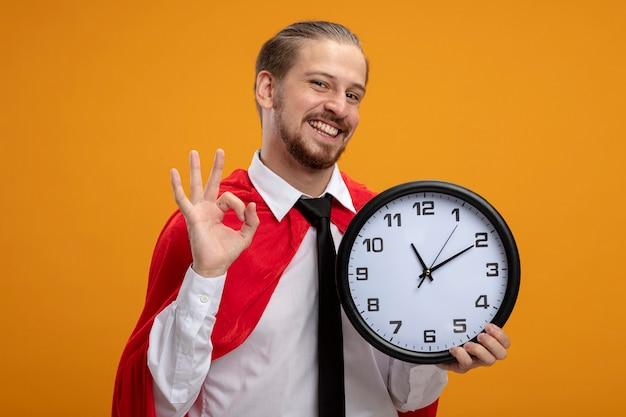 벽 시계를 들고 오렌지 배경에 고립 괜찮아 제스처를 보여주는 넥타이를 착용하는 젊은 슈퍼 히어로 남자 미소