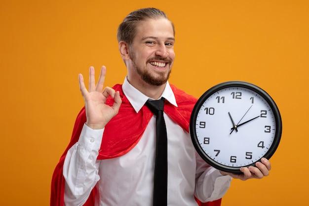 Sorridente giovane supereroe ragazzo indossa cravatta tenendo l'orologio da parete e mostrando il gesto giusto isolato su sfondo arancione