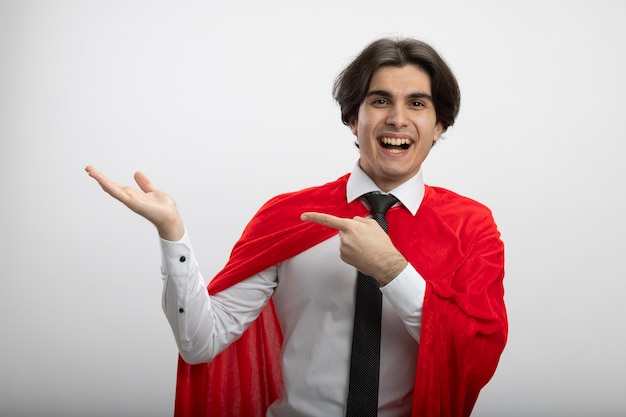 Smiling young superhero guy wearing tie pretending holding and points at something isolated on white
