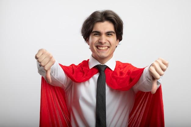 Улыбающийся молодой супергерой парень в галстуке показывает палец вниз на белом фоне