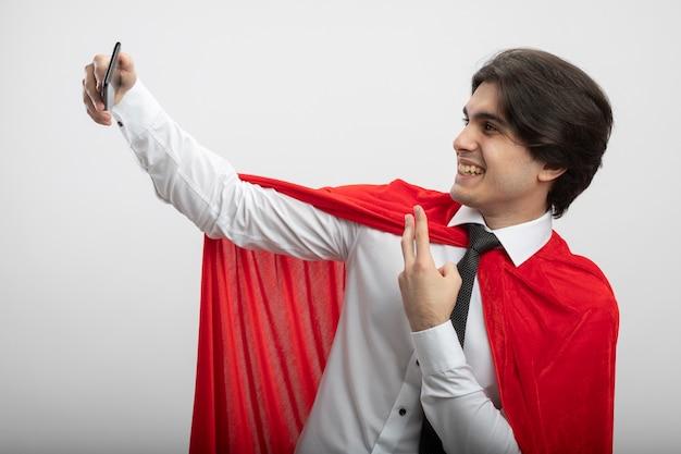 넥타이를 입고 웃는 젊은 슈퍼 히어로 남자는 셀카를 가지고 흰색 배경에 고립 된 평화 제스처를 보여주는