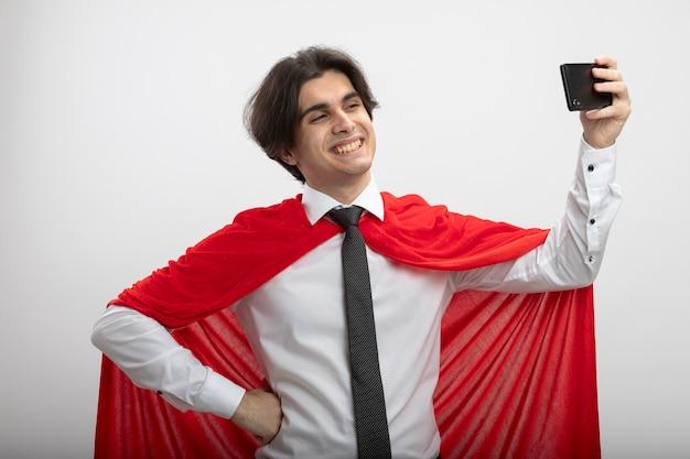 Sorridente giovane supereroe ragazzo indossa cravatta prendere aselfie e mettendo la mano sul fianco isolato su sfondo bianco