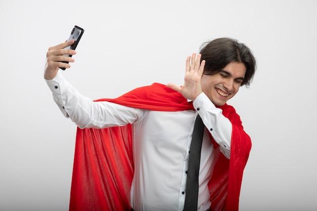 Улыбающийся молодой супергерой с закрытыми глазами в галстуке делает селфи и закрывает лицо рукой, изолированной на белом фоне