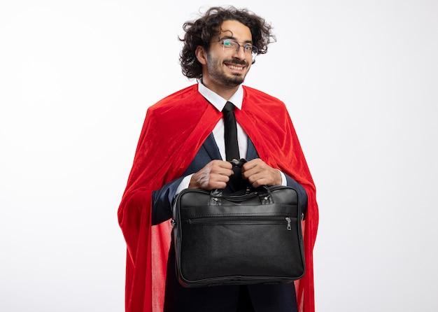 Sorridente giovane supereroe in vetri ottici che indossa tuta con mantello rosso tiene borsetta in pelle isolata sul muro bianco