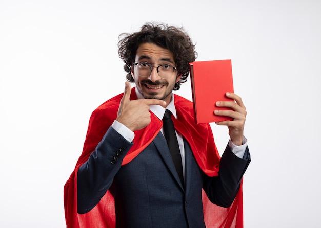 Sorridente giovane supereroe uomo in vetri ottici che indossa tuta con mantello rosso tiene e punti al libro isolato sulla parete bianca
